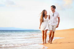 Beach couple walking on romantic travel. Honeymoon vacation summer holidays romance. Young happy lovers, Asian women and Caucasian men holding hands embracing Stock Image