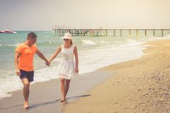 Beach couple walking on romantic travel honeymoon vacation summer holidays romance. Young happy lovers, Caucasian woman and man ho stock image