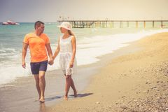 Beach couple walking on romantic travel honeymoon vacation summer holidays romance. Young happy lovers, Caucasian woman and man ho. Beach couple walking on stock images