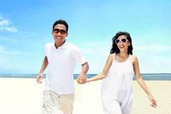 Beach couple in white dress running having fun laughing together. Portrait of beach couple in white dress running having fun laughing together Royalty Free Stock Photos