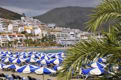 Beach of Cristianos at Tenerife. Umbrellas on the beach and town of Cristianos of the southern part of Tenerife in the Spanish Canary Islands Stock Photo