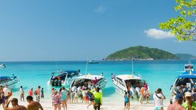 The beach crowded with tourists from different countries. People boarding a boats. SIMILAN ISLANDS, THAILAND - 15 MAR 2014: The beach crowded with tourists from stock footage
