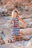 Beach cute girl posing on a rocky beach barefooted with curly hair wearing sailor dress and sun glasses.  royalty free stock photos