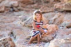 Beach cute girl posing on a rocky beach barefooted with curly hair wearing sailor dress and sun glasses.  royalty free stock photography