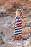 Beach cute girl posing on a rocky beach barefooted with curly hair wearing sailor dress and sun glasses.  stock photos