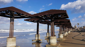 Beach damaged by water after storm, daylight, Mediterranean Sea, Haifa, Israel. Beach sunshades constructions damaged by water after storm, daylight, clouds Stock Photography