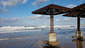 Beach damaged by water after storm, daylight, Mediterranean Sea, Haifa, Israel. Beach sunshades constructions damaged by water after storm, daylight, clouds Royalty Free Stock Photo