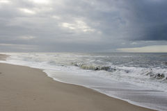 Beach with dark rain clouds Royalty Free Stock Image