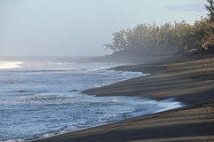 Beach with Dark Sand and Blue Sea of The Reunion Island. In the Morning Light with haze Stock Images