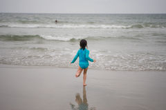 Beach Day. Brunette young girl running into the ocean Stock Photography
