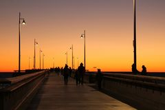 People walking on boardwalk at sunset stock image