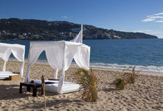 Beach Daybed. Daybed on sandy beach. This  canopied cabana appears to be for massage or relaxation. Acapulco bay in the background Stock Images