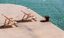 Beach deck chairs facing the sun at turquoise sea and rusty bollard royalty free stock photos