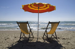 Beach. Deck chairs and beach umbrella by the sea Royalty Free Stock Images