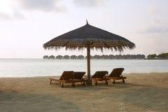 Beach deck chairs under straw umbrellas. Indian ocean coastline on Maldives island. White sandy beach and calm sea. Beach chairs under umbrellas. Indian ocean royalty free stock images