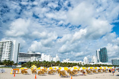 Beach with deck chairs under yellow umbrellas Stock Images