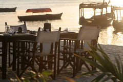 Beach Dining. Set dining table on tropical sandy beach at sunset with fishing boats in background, Zanzibar Island, Tanzania Royalty Free Stock Image