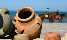 Beach on Djerba. Two riders and clay pots on the beach Royalty Free Stock Image