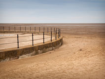 Beach and drained pool, Hoylake. Empty, circular pool with railings and beach with distant horizon. Hoylake on the Wirral coast, Merseyside Royalty Free Stock Photography