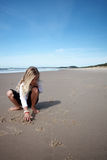 Beach drawings. A playful girl making drawings in the wet sand on a beach royalty free stock images