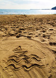 Beach dreams. Signs on a beach: a boat on the sea waves  drawn in the sand Stock Image