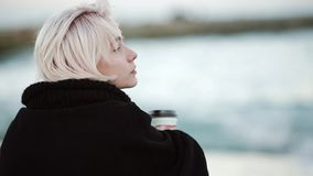 On the beach, she drinks coffee. She looks into the distance, straightens his hair. View from the back stock footage