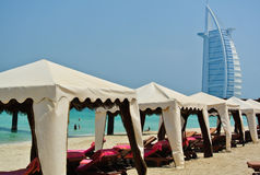 Beach in Dubai. Beach with tents and sunbeds in Dubai - United Arab Emirates. The Burj Al Arab on the background stock photography