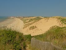 Beach and dunes on the North sea Opal coast, with the city of Wimereux in the distance. Under a clear blue sky, Nord PAs De calais, France royalty free stock photography