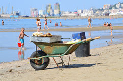 The beach of Durres. DURRES, ALBANIA – August 30, 2015: Left on the beach old wheelbarrow. On it a man grills and sales sweet corn. Albania has two faces Royalty Free Stock Images