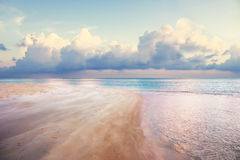 Beach on dusk with pink sand and pink perple water Stock Images