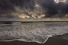 At the beach; early morning, landscape with large clouds away, and storm Royalty Free Stock Image