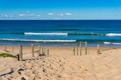 Beach entrance with blue ocean and soft waves Stock Photos
