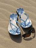 Beach essentials. Flip flops and sunglasses on the beach stock photography