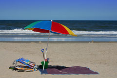 Beach Essentials. A colorful beach umbrellas with sand toys and beach chairs with the ocean waves and sand in the background on a clear summer day. Vacation royalty free stock image