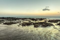 Beach in evening, after sunset during low tide showing sand form. Ations and rocks not covered by the sea. Klong Nin, Koh Lanta, Thailand Stock Photos
