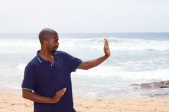 Beach exercise. Young african american man doing tai chi exercise on beach Stock Photo