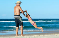 Beach family fun. Father and daughter enjoying some fun with the aeroplane game on the beach during the holidays stock photos