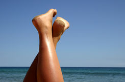 Beach Feet. Woman's legs and the sea Royalty Free Stock Images