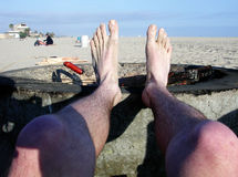 Beach feet. Sandy feet resting on firepit Royalty Free Stock Photos