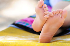 Beach feet. Closeup of feet of a young girl in chaise lounge relaxing on a beach Royalty Free Stock Photos