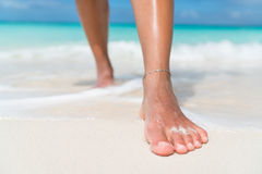 Beach feet closeup - woman walking in water waves. Beach feet closeup - barefoot woman walking in ocean water waves. Female young adult legs and toes wearing an Royalty Free Stock Photo