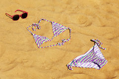 On the beach. Female swimwear and sunglasses lie on the sand on the beach Stock Photos