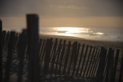 Beach Fence at Dawn. Sunrise Behind the Beach Wooden Fence Stock Image