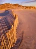 Beach fence on dunes at sunset stock photos