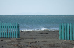 The beach and the fence. A light blue green fence on a beach Royalty Free Stock Image