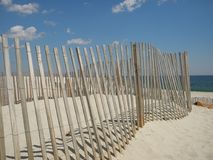 Beach Fence on New Jersey Shore. This is a beach fence on the New Jersey shore under a blue sky with cumulus clouds Royalty Free Stock Photos