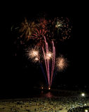 Beach Fireworks. Fireworks going off over beach front with crowd of people watching Royalty Free Stock Images