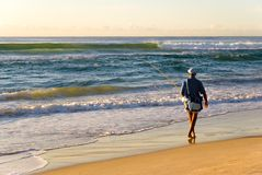 Beach Fisherman Surf Sunrise. Beach Fisherman fishing in ocean surf Royalty Free Stock Photo