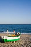 Beach and Fishing Boat. Two people play on a Spanish beach in front of a boat royalty free stock photography