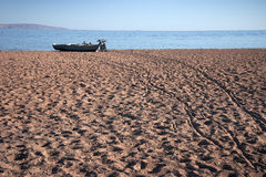 Beach with fishing boat and bikes Royalty Free Stock Photos